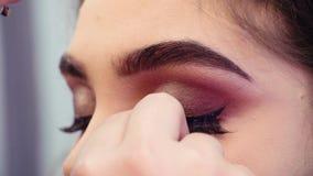 Καλλιτέχνης Makeup που κολλά τα ψεύτικα eyelashes στα μάτια απόθεμα βίντεο