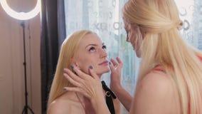 Καλλιτέχνης Makeup που προετοιμάζει το πρόσωπο μιας όμορφης γυναίκας πρίν ισχύει makeup απόθεμα βίντεο