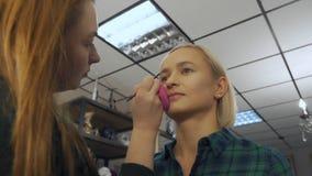 Καλλιτέχνης Makeup στην εργασία Θηλυκό visagist που χρησιμοποιεί brow τη βούρτσα Άκρες Makeup από τους επαγγελματίες φιλμ μικρού μήκους