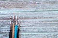 Καλλιτεχνικές βούρτσες σε ένα μπλε υπόβαθρο με μια ξύλινη σύσταση Στοκ φωτογραφία με δικαίωμα ελεύθερης χρήσης