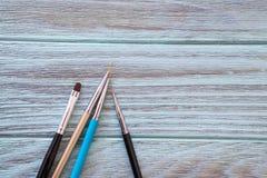 Καλλιτεχνικές βούρτσες σε ένα μπλε υπόβαθρο με μια ξύλινη σύσταση Στοκ Εικόνα