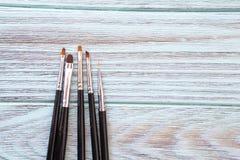 Καλλιτεχνικές βούρτσες σε ένα μπλε υπόβαθρο με μια ξύλινη σύσταση Στοκ Εικόνες