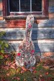 Καλλιτεχνική κιθάρα τσιμέντου που κλίνει ενάντια στο σπίτι κούτσουρων Στοκ εικόνες με δικαίωμα ελεύθερης χρήσης