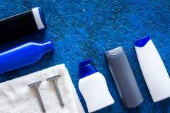 Καλλυντικά ατόμων ` s για την προσοχή και το ξύρισμα τρίχας Σαμπουάν, πήκτωμα, ξυράφι, κερί στην μπλε τοπ άποψη υποβάθρου copyspa Στοκ Εικόνες