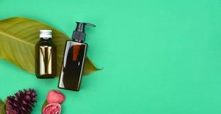Καλλυντικά εμπορευματοκιβώτια μπουκαλιών στο πράσινο βοτανικό υπόβαθρο φύλλων, κενή ετικέτα για το μαρκάρισμα του προτύπου, φυσικ Στοκ Εικόνες