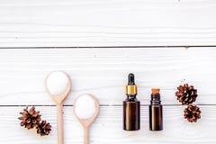 Καλλυντικά και aromatherapy έννοια Pine spa άλας, πετρέλαιο και pinecones στην άσπρη ξύλινη τοπ άποψη υποβάθρου copyspace Στοκ εικόνα με δικαίωμα ελεύθερης χρήσης