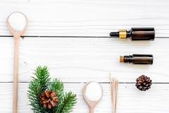 Καλλυντικά και aromatherapy έννοια Pine spa το άλας, το έλαιο, pinecones και οι ερυθρελάτες διακλαδίζονται στην άσπρη ξύλινη τοπ  Στοκ φωτογραφία με δικαίωμα ελεύθερης χρήσης