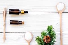 Καλλυντικά και aromatherapy έννοια Pine spa το άλας, το έλαιο, pinecones και οι ερυθρελάτες διακλαδίζονται στην άσπρη ξύλινη τοπ  Στοκ Εικόνες
