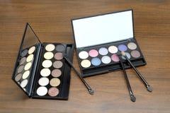 Καλλυντικά σύνολα με τις σκιές και τις βούρτσες ματιών σε μαύρη πλαστική περίπτωση με τον καθρέφτη στο ξύλινο υπόβαθρο Στοκ Φωτογραφίες