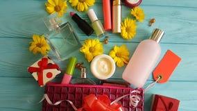 Καλλυντικά τσαντών καλλυντικά εμπορευματοκιβωτίων δερμάτων makeup διαφορετικά διακοσμητικά στα μπλε ξύλινα λουλούδια, αρώματα απόθεμα βίντεο
