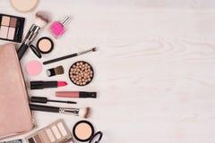Καλλυντικά Makeup και μια ανοικτή τσάντα στο άσπρο ξύλινο υπόβαθρο, τοπ άποψη με το διάστημα αντιγράφων στοκ εικόνες