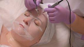 Καλλυντική διαδικασία για το του προσώπου μασάζ που χρησιμοποιεί μια ηλεκτρική συσκευή Μια γυναίκα σε μια άσπρη μάσκα είναι σε έν απόθεμα βίντεο