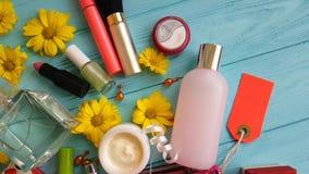 Καλλυντική ιτιά δερμάτων τσαντών makeup με τα διακοσμητικά καλλυντικά εμπορευματοκιβωτίων στα μπλε ξύλινα λουλούδια, αρώματα φιλμ μικρού μήκους