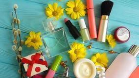 Καλλυντική ιτιά τσαντών makeup με τα διακοσμητικά καλλυντικά εμπορευματοκιβωτίων στα μπλε ξύλινα λουλούδια, αρώματα απόθεμα βίντεο