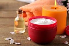 Καλλυντική κρέμα σε ένα κόκκινο βάζο της πετσέτας πετρελαίου κεριών στο υπόβαθρο σε έναν καφετή ξύλινο πίνακα SPA Χαλαρώστε στοκ εικόνες με δικαίωμα ελεύθερης χρήσης