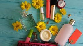 Καλλυντική τσάντα makeup με τα διακοσμητικά καλλυντικά στα μπλε ξύλινα λουλούδια, αρώματα απόθεμα βίντεο