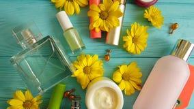 Καλλυντική τσάντα makeup με τα διακοσμητικά καλλυντικά εμπορευματοκιβωτίων στα μπλε ξύλινα λουλούδια, αρώματα απόθεμα βίντεο