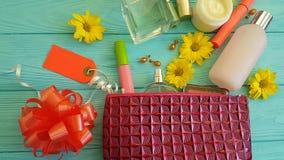 Καλλυντικό δέρμα τσαντών makeup με τα διακοσμητικά καλλυντικά εμπορευματοκιβωτίων στα μπλε ξύλινα λουλούδια, αρώματα απόθεμα βίντεο