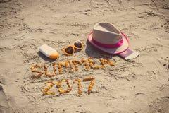 Καλοκαίρι 2017 επιγραφής, εξαρτήματα για την ηλιοθεραπεία και διαβατήριο με το δολάριο νομισμάτων στην παραλία Στοκ Φωτογραφία