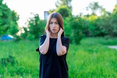 Καλοκαίρι κοριτσιών στο πάρκο στο καθαρό αέρα Χέρια που παρουσιάζουν μια χειρονομία που κλείνει τα αυτιά του Δυνατός θόρυβος της  Στοκ φωτογραφία με δικαίωμα ελεύθερης χρήσης