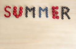 Καλοκαίρι ` λέξης ` που τοποθετούνται με τα μούρα σε έναν πίνακα Στοκ Εικόνες
