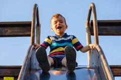 Καλοκαίρι, παιδική ηλικία, φιλία και έννοια ανθρώπων - το ευτυχές μικρό παιδί στην παιδική χαρά παιδιών γλίστρησε από το λόφο Στοκ φωτογραφίες με δικαίωμα ελεύθερης χρήσης