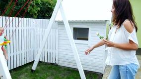 Καλοκαίρι, στον κήπο, μητέρα, όμορφη νέα γυναίκα, που ταλαντεύεται σε μια ταλάντευση τη 1χρονη κόρη της Η οικογένεια ξοδεύει φιλμ μικρού μήκους