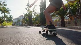 Καλοκαίρι στο κορίτσι νησιών στους γύρους longboard στα κοντά σορτς στο δρόμο κοντά στην παραλία και τους φοίνικες απόθεμα βίντεο