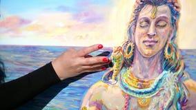 Καλοκαίρι, υπαίθρια, κινηματογράφηση σε πρώτο πλάνο των θηλυκών χεριών του καλλιτέχνη εφαρμόζει το χρώμα στον καμβά με τα δάχτυλά απόθεμα βίντεο