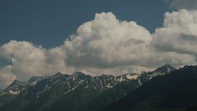 Καλοκαίρι χρόνος-σφάλματος Χιονώδεις αιχμές βουνών σε ένα κλίμα των άσπρων σύννεφων και ενός μπλε ουρανού Ταξίδι στα βουνά απόθεμα βίντεο