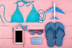καλοκαίρι women& x27 μόδα του s με το μπλε μαγιό, γυαλιά ηλίου, έξυπνο τηλέφωνο, ακουστικά, πτώσεις κτυπήματος, σημειωματάριο και Στοκ Φωτογραφίες