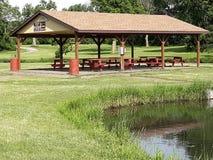 Καλυμμένη περιοχή πικ-νίκ στο πάρκο δίπλα στη λίμνη στοκ εικόνα