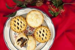 Καλυμμένος κομματιάστε τις πίτες στα Χριστούγεννα σε ένα κόκκινο επιτραπέζιο ύφασμα Στοκ Εικόνες
