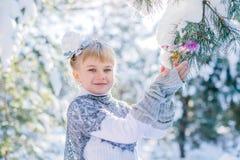 καλυμμένος χειμώνας ιστορίας χιονιού σπιτιών νεράιδων δασικός ξύλινος Το όμορφο μικρό κορίτσι περπατά σε ένα χιονώδες δάσος Στοκ Φωτογραφίες