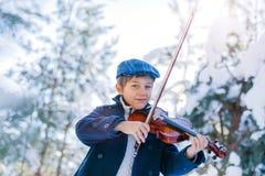 καλυμμένος χειμώνας ιστορίας χιονιού σπιτιών νεράιδων δασικός ξύλινος Χαριτωμένος βιολιστής αγοριών στο χειμερινό δάσος Στοκ Εικόνες