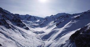 καλυμμένο χιόνι βουνών Πυροβολισμός με τον κηφήνα Άσπρο χιόνι στις γκρίζες και καφετιές πέτρες απόθεμα βίντεο