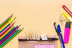 Καλωσορίστε πίσω στο σχολικό υπόβαθρο, το ζωηρόχρωμες μολύβι χρώματος και την τσάντα χαρτικών στα κίτρινα υπόβαθρα με το διάστημα στοκ φωτογραφία
