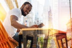 Καλός νεαρός άνδρας που χαμογελά διαβάζοντας ένα νέο μήνυμα από το φίλο του Στοκ φωτογραφία με δικαίωμα ελεύθερης χρήσης