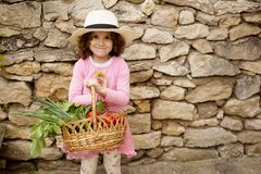 Καλός χαμογελώντας λίγο σγουρό κορίτσι τρίχας στο καπέλο, που κρατά ένα μεγάλο σύνολο καλαθιών με τα λαχανικά, που απομονώνεται σ στοκ φωτογραφίες