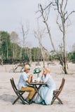 Καλό ασιατικό ζεύγος που έχει μια ρομαντική στιγμή της ευτυχίας υπαίθρια με τον πίνακα και την καρέκλα πικ-νίκ Στοκ Εικόνες