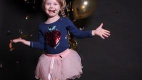 Καλό ευτυχές μικρό κορίτσι που πηδά με τα μπαλόνια κομφετί και αέρα στο υπόβαθρο φιλμ μικρού μήκους