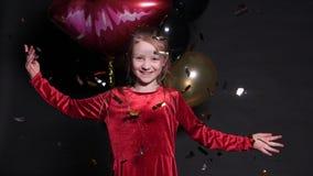 Καλό ευτυχές μικρό κορίτσι που πηδά με τα μπαλόνια κομφετί και αέρα στο υπόβαθρο απόθεμα βίντεο