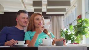 Καλό ζεύγος που απολαμβάνει το τσάι πρωινού στον καφέ μαζί, που κοιτάζει μακριά ονειρεμένα απόθεμα βίντεο