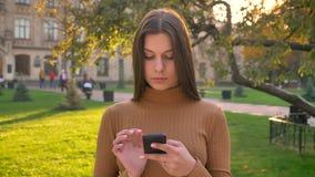 Καλό καυκάσιο κορίτσι που κάνει σερφ και που κουβεντιάζει χρησιμοποιώντας το smartphone και μεταβαλλόμενος τις συγκινήσεις στο πρ απόθεμα βίντεο