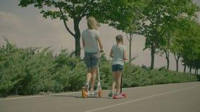 Καλό κορίτσι και mom στα μηχανικά δίκυκλα που έχουν τη διασκέδαση στο πάρκο απόθεμα βίντεο