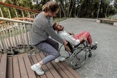 Καλό κορίτσι που βοηθά να ανυψώσει την αναπηρική καρέκλα με άκυρο στοκ εικόνες με δικαίωμα ελεύθερης χρήσης