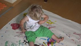 Καλό κοριτσάκι με τη ζωηρόχρωμη βούρτσα που χρωματίζει σε την τα ενδύματα φιλμ μικρού μήκους