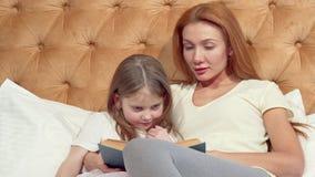 Καλό μικρό κορίτσι και το όμορφο mom της που χαμογελούν στη κάμερα, που διαβάζει ένα βιβλίο απόθεμα βίντεο