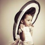 Καλό μικρό κορίτσι σε ένα μεγάλο μοντέρνο καπέλο Στοκ εικόνες με δικαίωμα ελεύθερης χρήσης