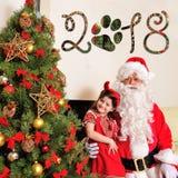 Καλό νέο πνεύμα έτους: Χριστουγεννιάτικο δέντρο, τσάντα δώρων, εστία και διακόσμηση για το έτος του σκυλιού Santa και ένα κορίτσι Στοκ Φωτογραφία